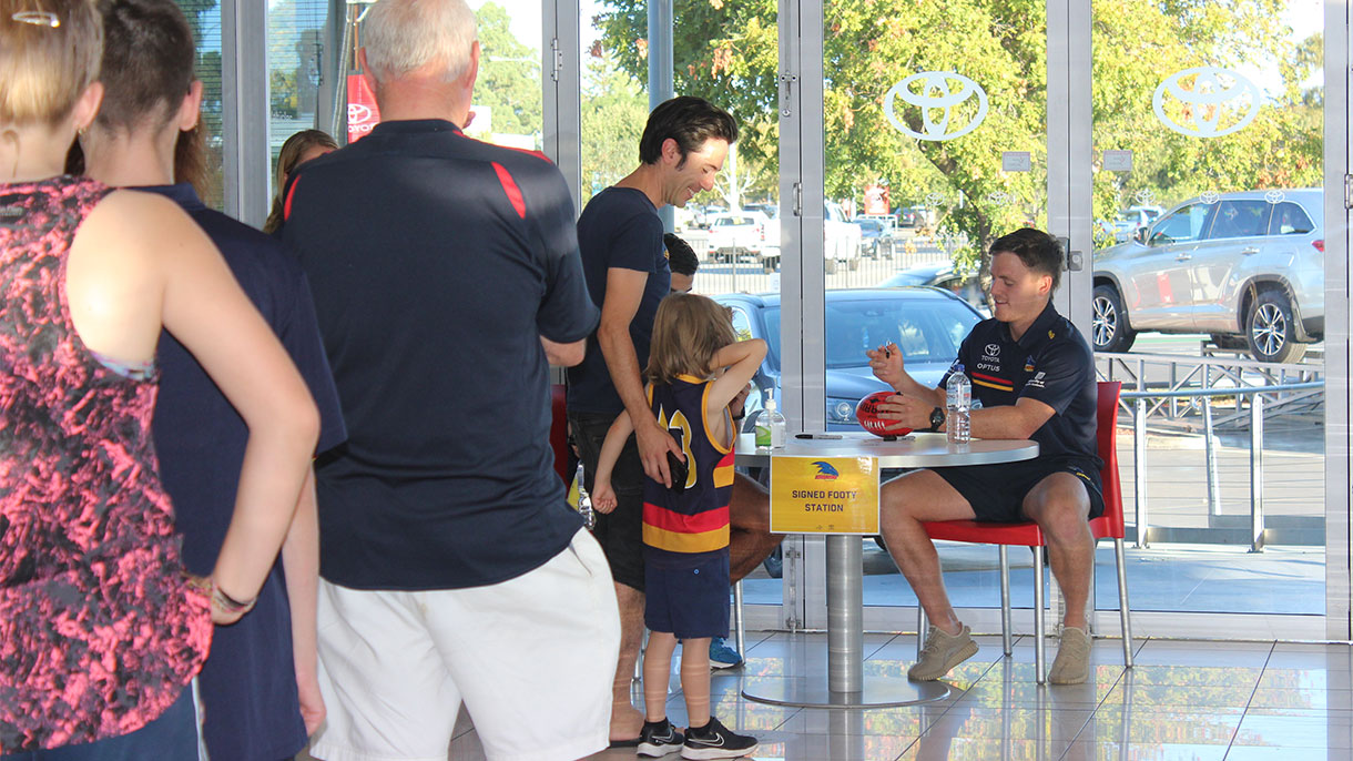 Adelaide Crows players signing footballs