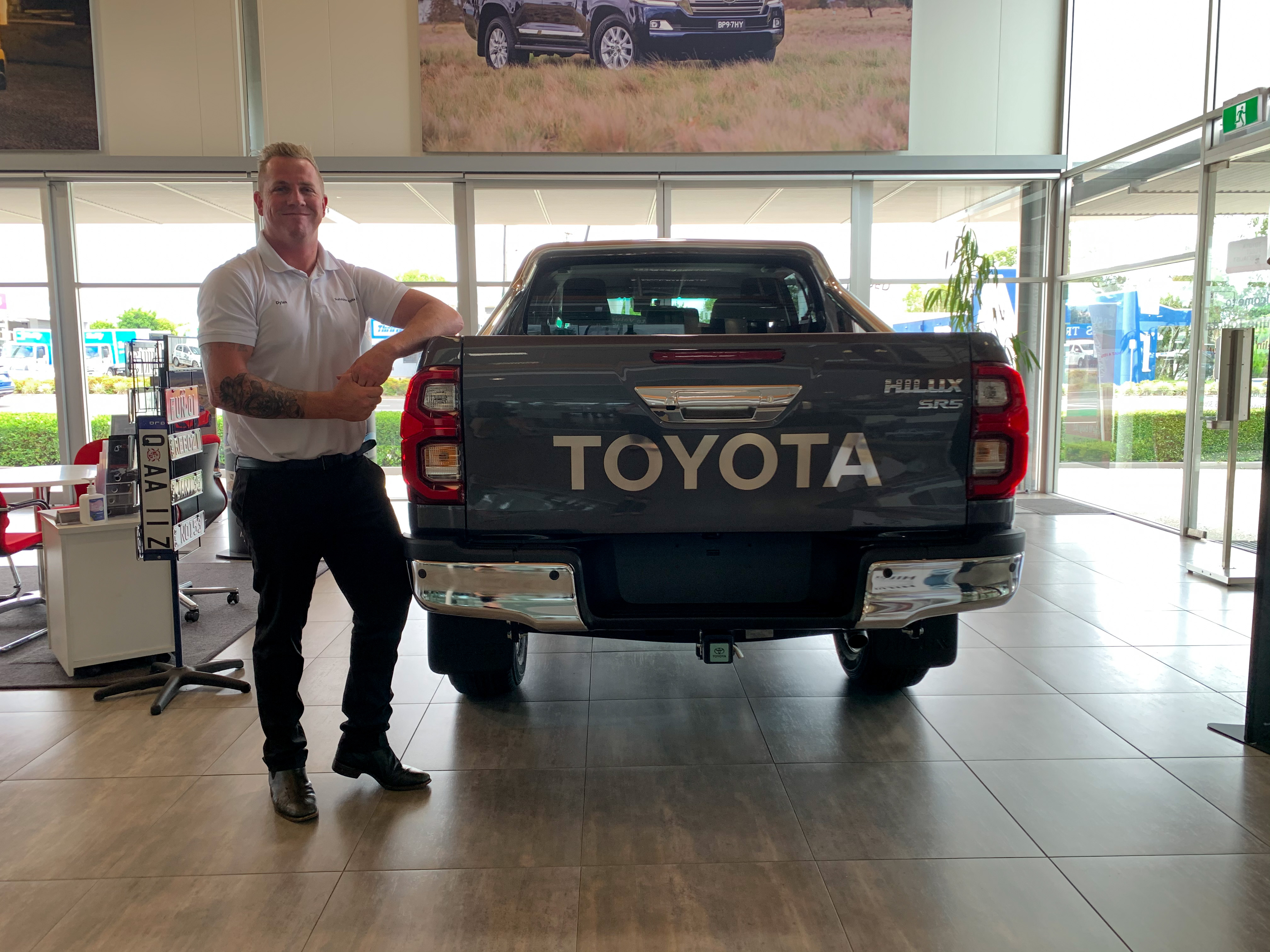 Dylan with a HiLux SR5 in graphite - ask us today at Sunshine Toyota on the Sunshine Coast